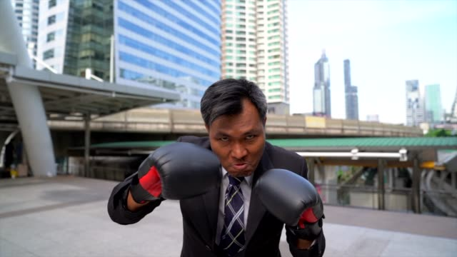 businessman punching with boxing gloves. concept of business competition.front view of businessman in boxing gloves against outdoor with cityscape as background. - colpire con un pugno video stock e b–roll