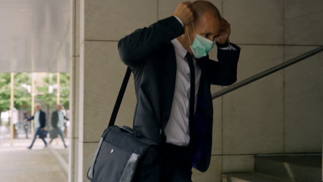 slo mo businessman putting on a mask while entering the office building - businessman covid mask video stock e b–roll
