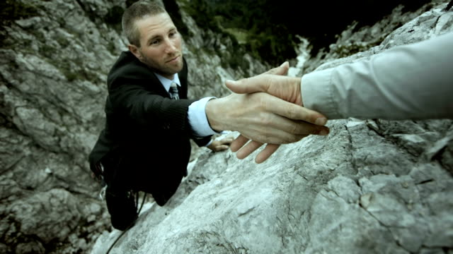 hd: businessman reaching for a helping hand - cliffs stock videos & royalty-free footage