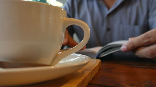 Businessman reading a book at coffee cafe video
