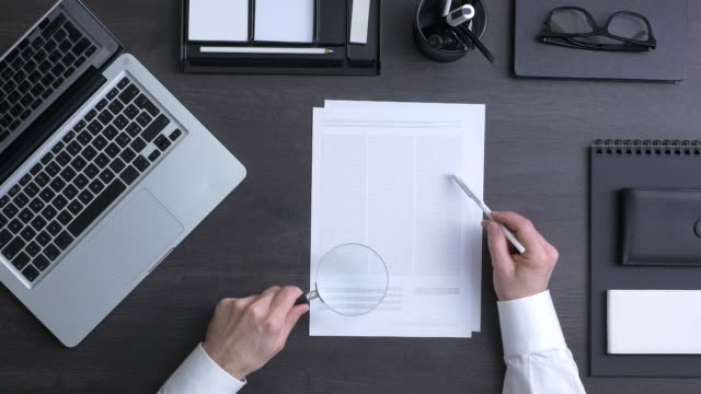 Businessman reading a contract Businessman reading carefully a contract and analyzing terms and conditions with a magnifier, top view magnifying glass stock videos & royalty-free footage
