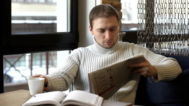 affärs man läser en tidning på en fika paus - paper mass bildbanksvideor och videomaterial från bakom kulisserna