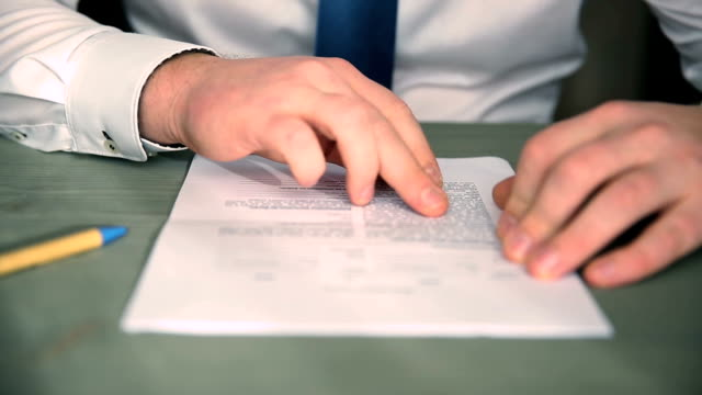 vídeos de stock e filmes b-roll de businessman reading and signing business partnership contract in office - contrato