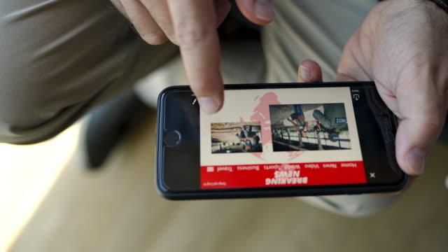 Businessman reading breaking news on his smart phone on the break video