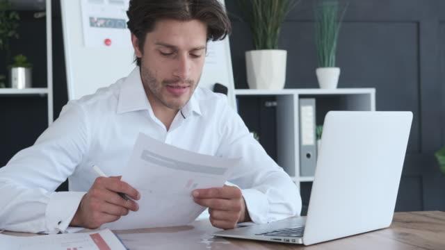 ラップトップでビデオ会議を行っている間、ビジネスマンがドキュメントを読む - オンライン会議点の映像素材/bロール