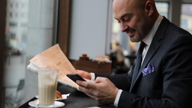 Businessman reading newspaper and texting in cafe video