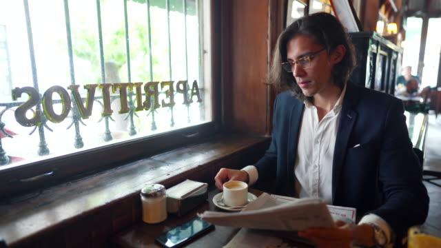 stockvideo's en b-roll-footage met zakenman die kranten over koffie na het werk in lokaal koffie leest - lang haar
