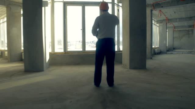 vídeos y material grabado en eventos de stock de hombre de negocios, inmobiliaria, inversor en casco en construcción sin terminar. rascacielos en construcción - imperfección