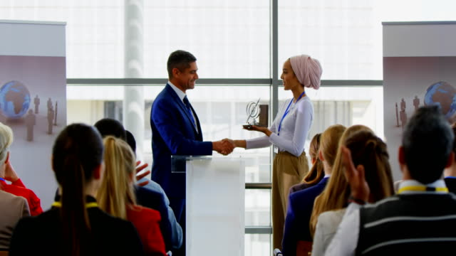 vídeos de stock, filmes e b-roll de homem de negócios que recebe uma concessão de uma mulher de negócios no seminário 4k do negócio - prêmio