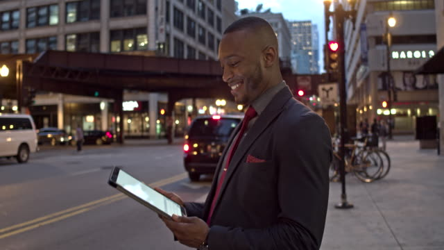 Businessman receiving good news on digital tablet Businessman receiving good news on digital tablet while commuting in Chicago. good news stock videos & royalty-free footage