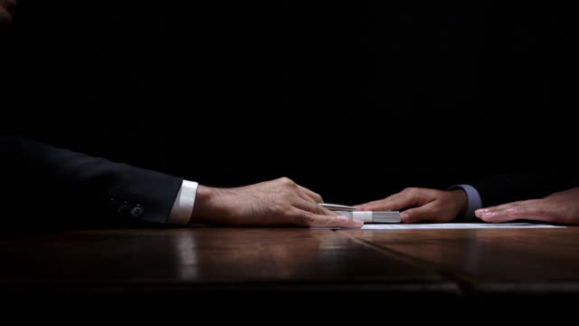 Businessman receiving money from partner and signing contract in dark room Businessman receiving bribe money from partner after making a deal and signing confidential contract paper in dark room fraud stock videos & royalty-free footage