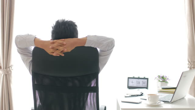 Businessman Relaxing after hard work in office , relaxation concept , UHD Format video