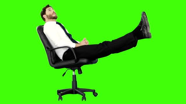 vídeos de stock e filmes b-roll de empresário relaxante na sua cadeira com pernas de - chair