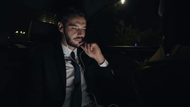 seyahat ederken rahatlatıcı bir iş adamı. - kulak i̇çi kulaklık stok videoları ve detay görüntü çekimi