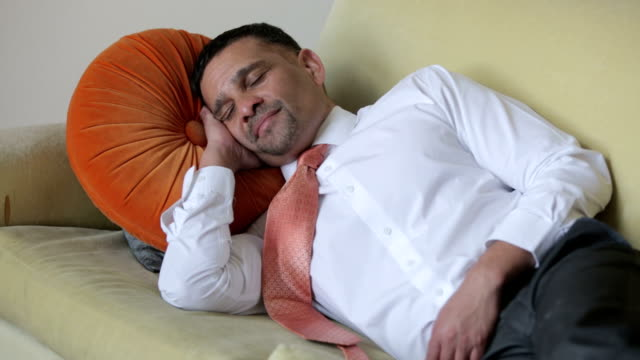 businessman resting and yawning on a couch video