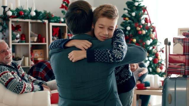 stockvideo's en b-roll-footage met zakenman keert terug naar huis van een zakenreis op een kerstdag - christmas family