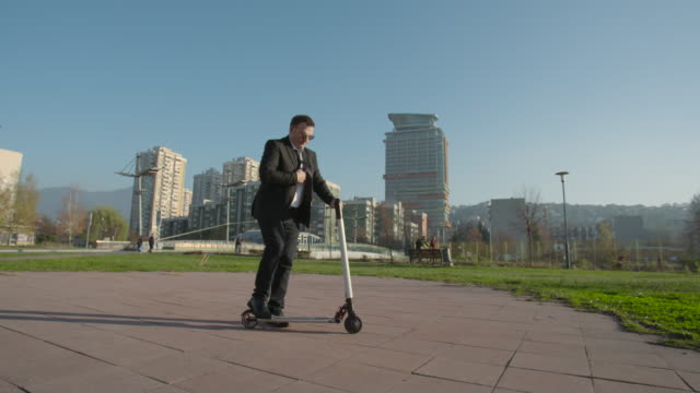 businessman riding a scooter through city - monopattino elettrico video stock e b–roll