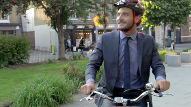 Businessman Riding Bike Through City Park Businessman riding bike through urban park.Shot on Canon 5D MkII at a frame rate of 25fps work helmet stock videos & royalty-free footage