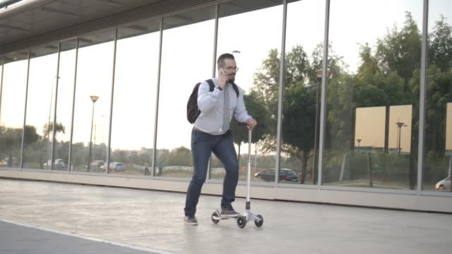 4 k : ビジネスマン乗馬プッシュスクーターです。 - 全身点の映像素材/bロール