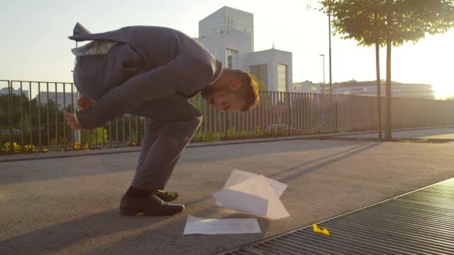 vidéos et rushes de gros plan: homme d'affaires déchirures son pantalon pour cueillir les documents - homme slip