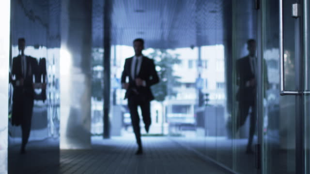 Businessman Running on Streets of Business District. Slow Motion Shot. video