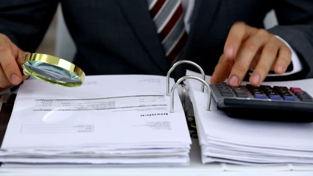 Businessman Scrutinizing Invoice With Magnifying Glass video