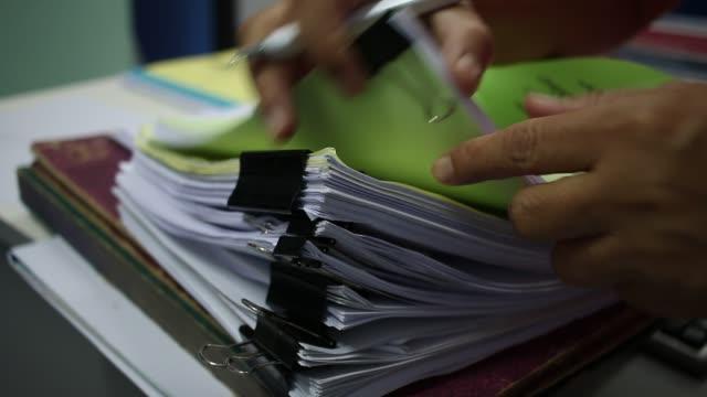 affärsman söka dokument filer eller information i högen av papper mapp på arbete i office, business rapport papper eller högar av oavslutade dokument uppnår med klipp på kontor, affärsidé - lagbok bildbanksvideor och videomaterial från bakom kulisserna
