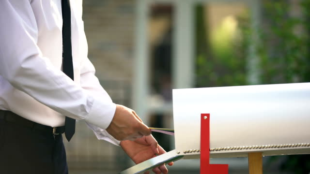 Businessman sending letters and bills, putting them into mailbox near house Businessman sending letters and bills, putting them into mailbox near house post office stock videos & royalty-free footage