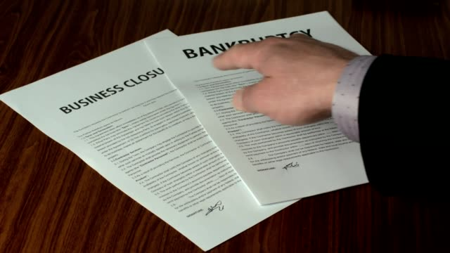 Businessman Showing A Business Closure Documentation In Close Up. video