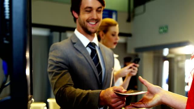 チェックイン カウンターで搭乗券を彼を示す実業家 ビデオ