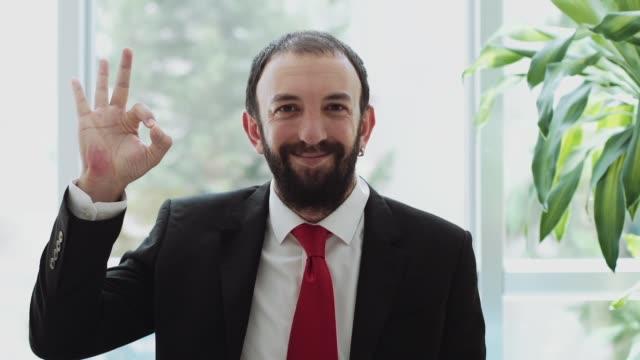 businessman showing ok sign, indoor - znak ok filmów i materiałów b-roll