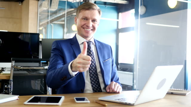 Businessman showing thumbs up video