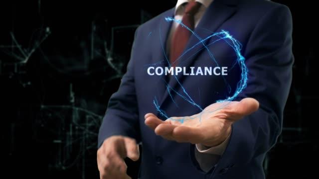 vidéos et rushes de homme d'affaires montre hologramme notion conformité sur sa main - uniforme