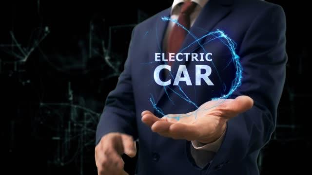 businessman shows concept hologram electric car on his hand - intercity filmów i materiałów b-roll