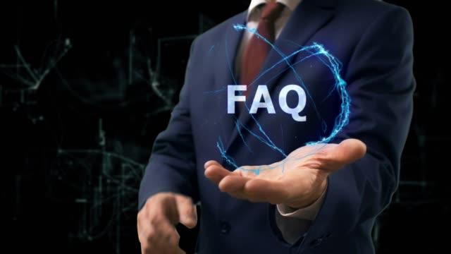 vídeos y material grabado en eventos de stock de hombre de negocios muestra el concepto del holograma faq en su mano - faq