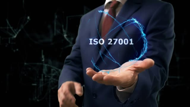 Businessman shows concept hologram ISO 27001 on his hand