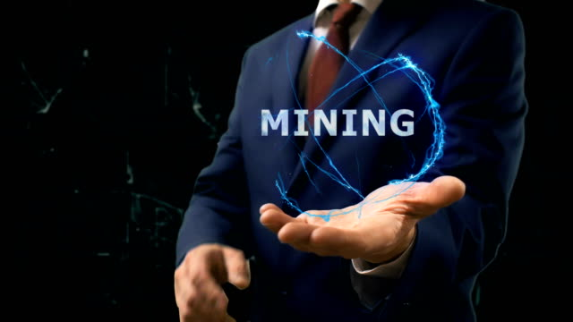 Businessman shows concept hologram Mining on his hand video