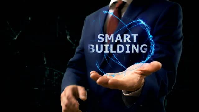 Businessman shows concept hologram Smart building on his hand video