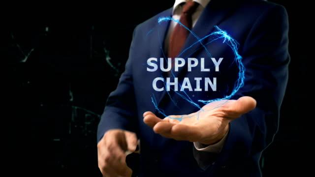 Empresario muestra el holograma del concepto cadena de suministro en su mano - vídeo