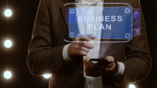 Businessman shows hologram with text Business plan