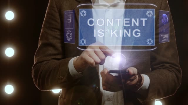 Businessman shows hologram with text Content is King