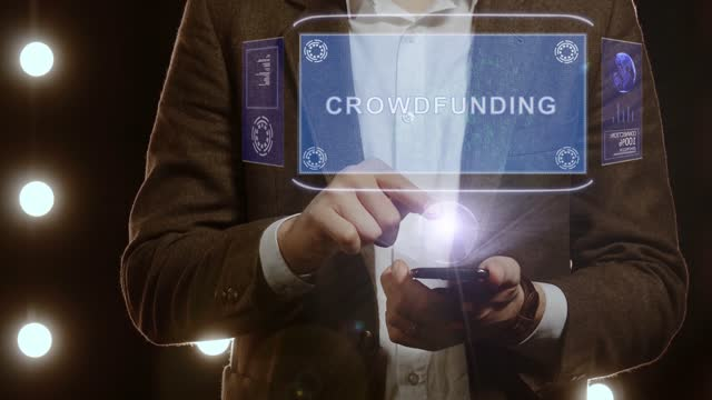 Businessman shows hologram with text Crowdfunding