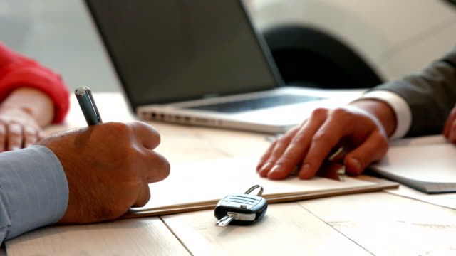 Businessman siging some documents Businessman siging some documents at the car showroom car key stock videos & royalty-free footage