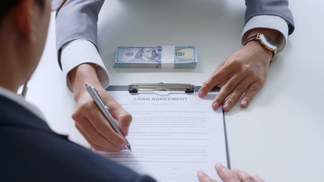 Businessman sign on money loan agreement contract to banker, loan and credit financial lease concept Businessman sign on money loan agreement contract to banker, loan and credit financial lease concept mortgages and loans stock videos & royalty-free footage