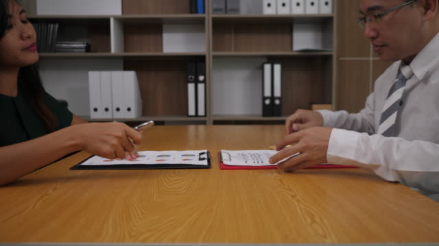 Businessman signing a contract paper and deal some business - video