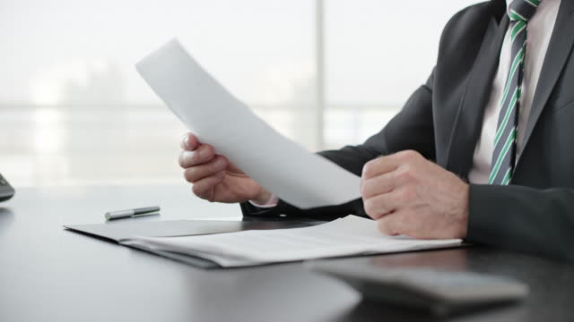 businessman signing a document in his office - firma video stock e b–roll