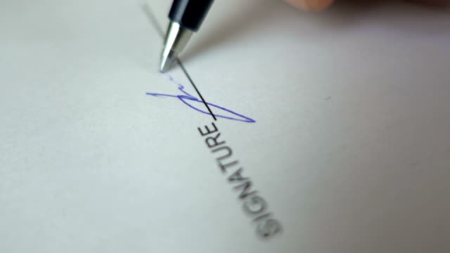 Businessman signing business contract agreement, close up of male hand with pen writing signature