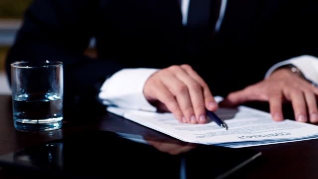 Businessman signs a number of document video