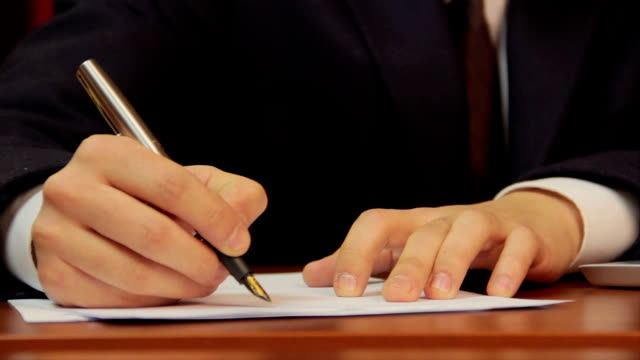 Businessman signs papers, contract, agreement, works on laptop video