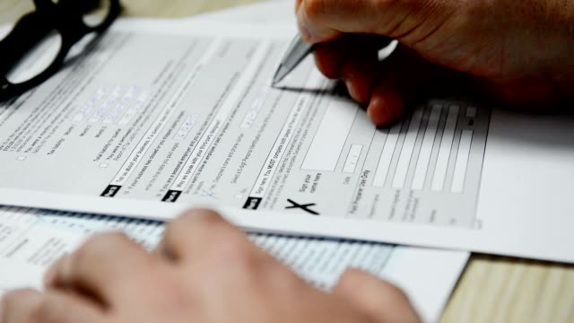 Businessman signs tax form 1040 video